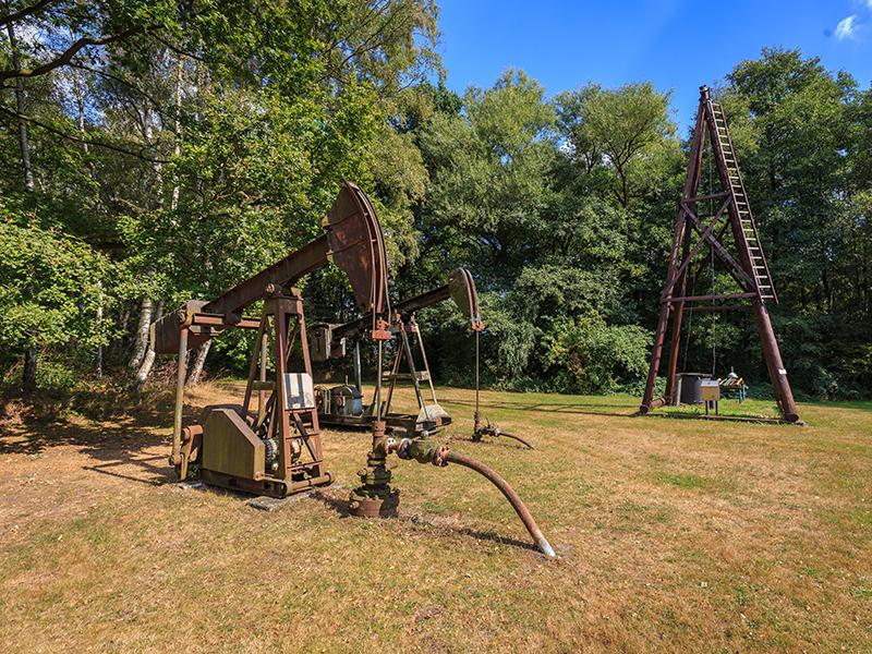 Alte Maschinen zum Abschöpfen des Teers stehen auf einer Wiese.