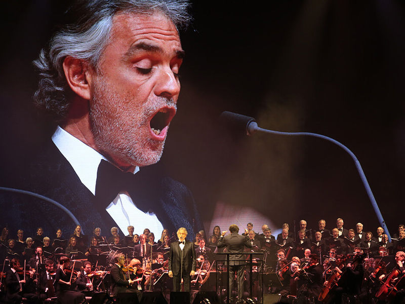 A stage with a large orchestra in front of a huge screen showing an man singing into a microphone.
