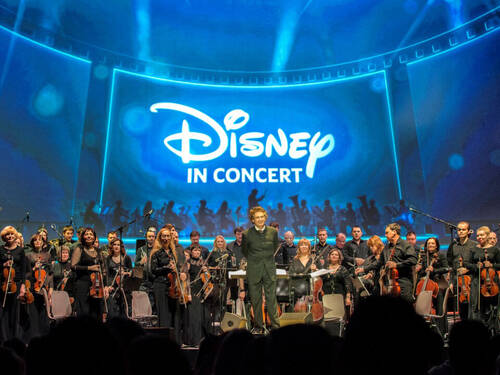 An orchestra and its conductor on a stage in front of with a large screen