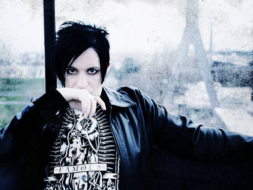 Man in a black leather jacket with short black hair and heavily kajalized eyes