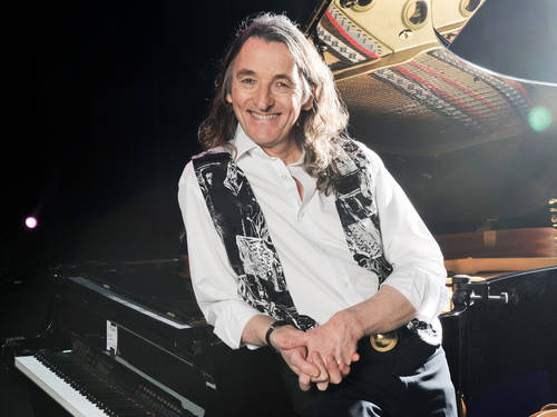 A smiling man with long hair leaning against a grand piano.