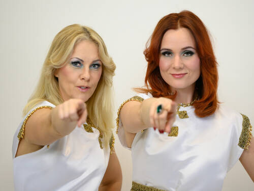 A blond and a red-haired woman pointing at the camera