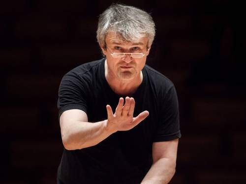 A grey-haired man in a conductor's pose.