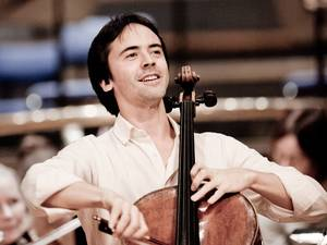 A dark-haired man playing the cello.