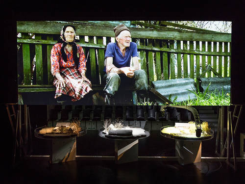Three tables with house models on a stage in front of a screen showing the picture of an old couple.