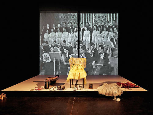 Women's clothing and shoes on a stage in front of a photo of a choir