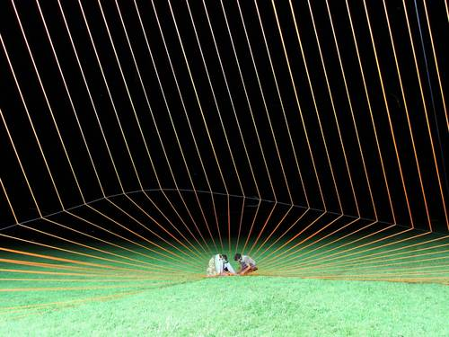 Two people on a lawn amid a net-like structure of bright green ropes.