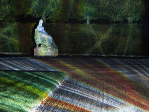 A white staue of a sitting woman in a park illuminated with colourful stripes.
