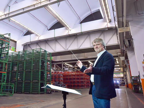 Man with conductor bar in large factory hall
