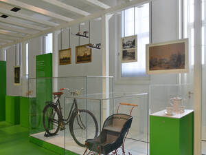 A view of the garden wing in Herrenhausen Palace Museum: there is an old bicycle in the centre of the picture accompanied by an old pram, in the background there are several paintings